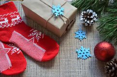 стекло состава рождества bauble голубое Подарок рождества, связанное одеяло, конусы сосны, ель разветвляет на деревянной белой пр Стоковое Изображение