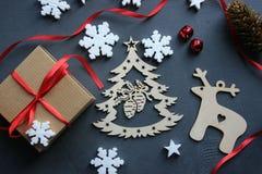 стекло состава рождества bauble голубое Подарочная коробка с красными лентой, деревом и снежинками сатинировки на черной предпосы стоковая фотография