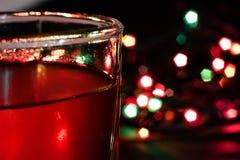 Стекло с алкогольным напитком против предпосылки покрашенных светов Стоковое Фото
