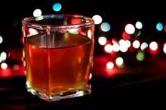 Стекло с алкогольным напитком против предпосылки покрашенных светов Стоковые Фото