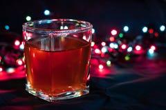 Стекло с алкогольным напитком против предпосылки покрашенных светов Стоковое Изображение
