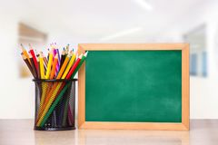 Стекло с карандашами и школьное правление для записи на деревянном столе стоковое изображение rf