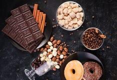 Стекло с кофейными зернами рядом с таблетками шоколада, donuts, желтым сахарным песком и другим стеклом с арахисами в шоколаде Стоковое фото RF