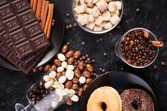 Стекло с кофейными зернами рядом с таблетками шоколада, donuts, желтым сахарным песком и другим стеклом с арахисами в шоколаде Стоковое Изображение
