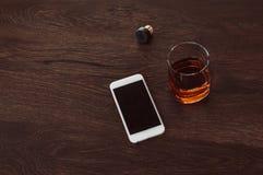 Стекло с ложью вискиа, пробочки и мобильного телефона на деревянном столе стоковое изображение rf