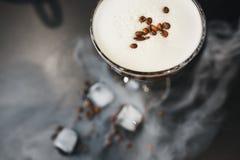 Стекло с напитком кофе, белым crema, кофейными зернами, черной предпосылкой, кубами льда конец вверх Взгляд сверху стоковые фото