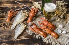 Стекло с пивом и бутылкой пива и посоленных кипеть красных раков на холсте Стоковое Фото