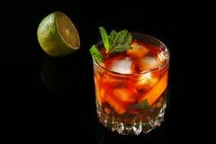 Стекло темного коктейля рома с известкой, апельсином, кубами льда и листьями мяты на черной предпосылке зеркала стоковая фотография rf