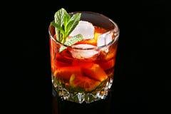 Стекло темного коктейля рома с известкой, апельсином, кубами льда и листьями мяты на черной предпосылке зеркала стоковые изображения