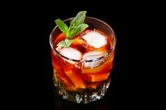 Стекло темного коктейля рома с известкой, апельсином, кубами льда и листьями мяты на черной предпосылке зеркала стоковое изображение