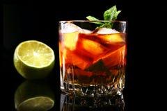 Стекло темного коктейля рома с известкой, апельсином, кубами льда и листьями мяты на черной предпосылке зеркала стоковая фотография