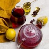 Стекло чая гибискуса с лимоном, чайником, медом на белой предпосылке Состав Teatime concept healthy lifestyle стоковая фотография rf