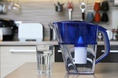 Стекло чистой воды и фильтра для очищая питьевой воды на таблице в кухне Очищение питьевой воды дома стоковое фото