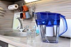 Стекло чистой воды и фильтра для очищая питьевой воды на таблице в кухне Очищение питьевой воды дома стоковые изображения