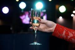 Стекло шампанского в руке ` s женщины на расплывчатой предпосылке с bokeh стоковое фото rf