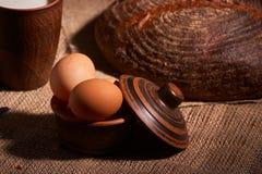 стекло яя, хлеба и молока на деревянном столе и темной деревянной предпосылке Селективный фокус стоковое изображение
