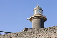 Стеклянная верхняя башня маяка на серой каменной стене, Jandia, Канарских островах Стоковое Изображение RF