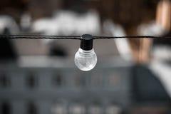 Стеклянная лампа с черным основанием на предпосылке домов Электрическая лампочка вверх r r стоковые фотографии rf