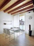 Стеклянная обедая таблица в самомоднейшей квартире Стоковые Изображения