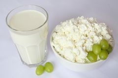Стеклянная чашка с молоком, белым блюдом фарфора с творогом, зелеными виноградинами Стоковое Изображение