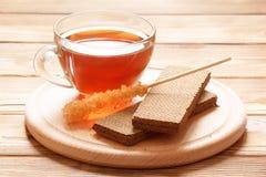 Стеклянная чашка чаю с waffles шоколада кудрявыми и тростниковый сахар вставляют на деревянном блюде Стоковые Изображения