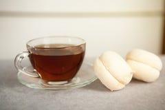 Стеклянная чашка черного чая и помадок или macaroons на таблице Стоковая Фотография