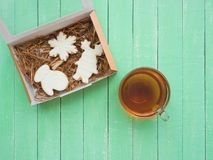 Стеклянная чашка черного чая и пряника с поливой на цвета мят деревянном столе Стоковая Фотография RF