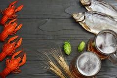 Стеклянное пиво с раками, высушенными рыбами и ушами пшеницы на темной деревянной предпосылке Концепция винзавода пива пиво предп Стоковая Фотография