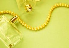 Стеклянные бутылки женского дух на зеленой предпосылке Стоковые Фотографии RF