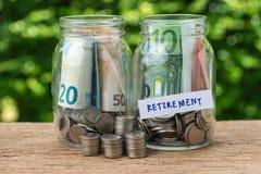 стеклянные бутылки опарника обозначенные как выход на пенсию с вполне монеток и b Стоковые Изображения RF