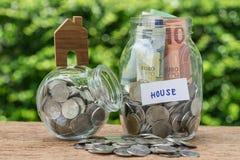 Стеклянные бутылки опарника обозначенные как дом с вполне монеток и bankno Стоковое Фото