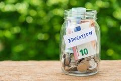 Стеклянные бутылки опарника с вполне монеток обозначенных как образование как edu Стоковое Изображение