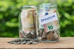 Стеклянные бутылки опарника с вполне монеток обозначенных как образование как edu Стоковая Фотография