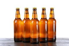 Стеклянные бутылки пива на предпосылке белизны таблицы Стоковая Фотография RF