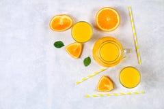 Стеклянные бутылки, стекла и кувшин свежего апельсинового сока с кусками оранжевых и желтых трубок на свете - серой таблицы Взгля Стоковая Фотография RF