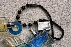 Стеклянные бутылки с духами и черные шарики на серой предпосылке Стоковые Фото