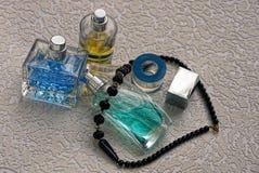 Стеклянные бутылки с духами и черные шарики на серой предпосылке Стоковое Изображение