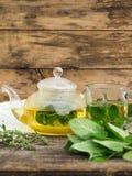 Стеклянные чайник и чашка с травяным чаем Стоковое Изображение