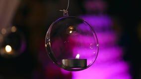 Стеклянные шарики с свечами висят перед окном сток-видео