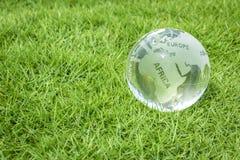 Стеклянный глобус на зеленой траве стоковое фото