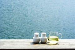 Стеклянный опарник горячего чая и комплект белых керамических чашек Стоковое Фото
