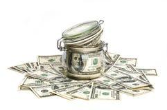 Стеклянный опарник заполнил с долларами среди 100 долларовых банкнот на белой предпосылке Стоковое Изображение