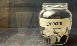 """Стеклянный опарник с монетками и надписью """"мечта """" Семейный бюджет и финансы Распределение сбережений наличных денег Выполняя лел стоковое изображение"""