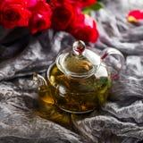 Стеклянный чайник на темной предпосылке Красные розы рядом Стоковые Фото