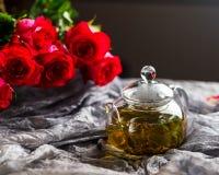 Стеклянный чайник на темной предпосылке Красные розы рядом Стоковая Фотография