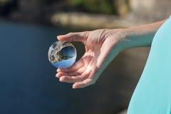 Стеклянный шарик в руке, внешней, фокусе на коже, ландшафте sunligh Стоковые Изображения