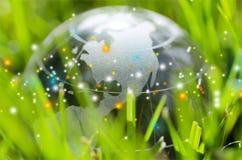 Стеклянный шарик глобуса в световых лучах на предпосылке травы Стоковая Фотография