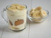 Стеклянный шар с частями банана и пудинга банана в чашке на белой таблице Стоковое Изображение