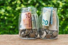 2 стеклянных бутылки опарника с вполне монеток и банкнот евро с g Стоковое Изображение RF