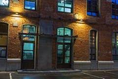 2 стеклянных двери в кирпичном здании в ноче, старом доме кирпича Взгляд ночи в старом промышленном квартале moscow hamburg стоковое изображение